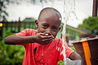 boy drinking water from his hand